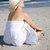 content blonde in white dress sitting on the beach stock photo © wavebreak_media
