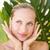mooie · blond · glimlachend · camera · achter · blad - stockfoto © wavebreak_media