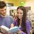 glimlachend · vrienden · student · lezing · leerboek · boekenkast - stockfoto © wavebreak_media