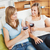 Charming two women drinking wine sitting on a sofa in the living-room stock photo © wavebreak_media