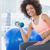 smiling young woman exercising with dumbbell in gym stock photo © wavebreak_media