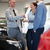 salesman giving car keys to a couple in front of an open car engine stock photo © wavebreak_media