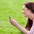 Delighted young woman writing a message on her phone sitting on the grass stock photo © wavebreak_media