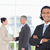 young smiling executive standing upright in a suit with business people behind him stock photo © wavebreak_media