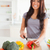 Pretty female cooking vegetables while standing in the kitchen stock photo © wavebreak_media