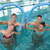 happy fitness class doing aqua aerobics with foam rollers stock photo © wavebreak_media