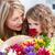 Little girl smelling flowers while her grandmother is smilling stock photo © wavebreak_media