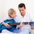 smiling little boy playing guitar with his father stock photo © wavebreak_media