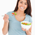 Good looking woman eating a bowl of salad while standing against a white background stock photo © wavebreak_media