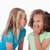 girl whispering a secret to her friend against a white background stock photo © wavebreak_media