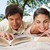 Man and a woman smiling while reading books together as they are lying prone on a blanket in the gra stock photo © wavebreak_media