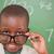 smiling schoolboy looking over his glasses in front of a blackboard stock photo © wavebreak_media