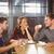 smiling friends talking and enjoying coffee and cake stock photo © wavebreak_media