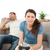 Serious woman playing video game while her boyfriend waiting for her on the sofa at home stock photo © wavebreak_media
