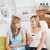 Cheerful two women drinking coffee and talking while sitting on a sofa at home stock photo © wavebreak_media
