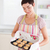 smiling brunette woman showing muffins in a kitchen stock photo © wavebreak_media