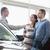 smiling salesman handing keys to a couple in a car shop stock photo © wavebreak_media