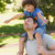smiling man carrying son on his shoulders in park stock photo © wavebreak_media