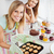Happy female friends holding cookies in the kitchen at home stock photo © wavebreak_media