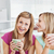 Positive female friends holding a cup of coffee at home in the living-room stock photo © wavebreak_media