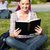 Serious female student reading a book sitting on grass at her campus university stock photo © wavebreak_media
