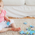Lovely baby playing with puzzle pieces while sitting on a carpet in the living room stock photo © wavebreak_media