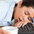 Good looking woman sleeping on a keyboard while holding a cup of coffee at the office stock photo © wavebreak_media