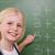 Blonde schoolgirl pointing at something on a blackboard stock photo © wavebreak_media