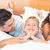 cute young family lying on bed together smiling stock photo © wavebreak_media
