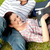 Couple of cheerful students using a laptop lying on the grass at their campus university stock photo © wavebreak_media