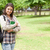 Young student holding textbook while standing in a park stock photo © wavebreak_media