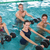 happy fitness class doing aqua aerobics with foam dumbbells stock photo © wavebreak_media