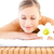 close up of a delighted woman lying on a massage table with a flower in a health spa stock photo © wavebreak_media