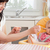 attractive brunette woman feeding her baby while sitting in the kitchen stock photo © wavebreak_media
