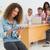 smiling designer sitting in front of her colleagues using digita stock photo © wavebreak_media