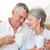 senior couple sitting on couch drinking coffee touching heads stock photo © wavebreak_media