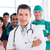Atractive doctor standing with his colleagues in a hospital stock photo © wavebreak_media