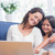 happy mother and daughter sitting on the couch and using laptop stock photo © wavebreak_media