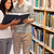 portrait of happy students reading a book in a library stock photo © wavebreak_media