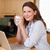 Woman with laptop and a cup in the kitchen stock photo © wavebreak_media