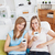Relaxed two women drinking coffee smiling at the camera sitting on a sofa stock photo © wavebreak_media