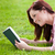 Kind young woman reading a book lying on the grass stock photo © wavebreak_media