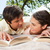 Man and a woman looking at each other while reading books as they lie prone on a grey blanket in the stock photo © wavebreak_media