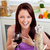 Cheerful woman eating her meal holding a glass of wine at home in the kitchen stock photo © wavebreak_media