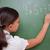 Schoolgirl writing a result on a blackboard stock photo © wavebreak_media