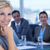 businesswoman smiling at camera with colleagues behind stock photo © wavebreak_media
