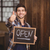 smiling casual waiter showing chalkboard and thumbs up stock photo © wavebreak_media