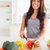 Beautiful female cooking vegetables while standing in the kitchen stock photo © wavebreak_media