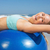 fit woman lying on exercise ball at the beach stretching stock photo © wavebreak_media