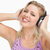 smiling blonde woman wearing headphones while touching them against a white background stock photo © wavebreak_media